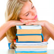 Tired girl sitting at desk and sleeping on piles of books — Stock Photo