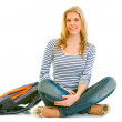 Smiling young girl with schoolbag sitting on floor — Stock Photo #8638848