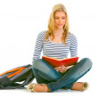 Pensive teengirl with schoolbag  sitting on floor and reading book — Stock Photo