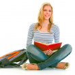 Stock Photo: Smiling teen girl with backpack sitting on floor and reading sch