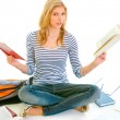 Shocked teen girl sitting on floor with books and  preparing for exams - Stock Photo