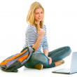 Pleased teengirl sitting on floor with schoolbag and laptop — Stock Photo #8638968
