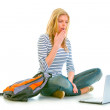 Amazed teen girl sitting on floor with backpack and looking on laptop — Stock Photo #8638974