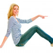 Smiling beautiful teen girl sitting on floor and pointing finger at somethi — Stock Photo #8639040