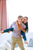 Happy girl piggy backing her boyfriend — Stock Photo
