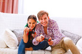 Cheerful young couple playing console — Stock Photo
