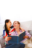 Laughing young couple sitting on couch and looking in photo albu — Stock Photo