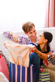 Young guy helping her girlfriend to choose dress — Foto Stock