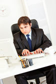 Thoughtful businessman sitting at office desk and working on computer — Stock Photo