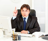 Concentrated businessman with rised finger sitting at office desk. Idea ges — Stock Photo