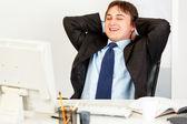 Laughing businessman sitting at office desk and looking at computers monito — Stock Photo