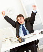 Excited businessman sitting at office desk and rejoicing his success — Stock Photo
