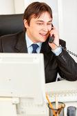 Úspěšný podnikatel moderní sedí v kanceláři a na telefonu — Stock fotografie