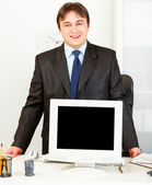Smiling businessman standing at office desk and showing monitors blank scre — Stock Photo