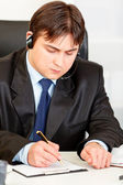 Concentrated businessman with headset sitting at office desk and taking n — Stock Photo