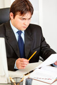 Serious businessman sitting at office desk and intently looking at document — Stock Photo