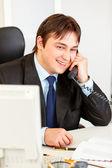 Улыбаясь современного бизнесмена, сидя на офисный стол и разговаривает по телефону — Стоковое фото
