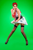 Flirty looking sensual girl holding dress blown up by wind. Pin-up and retr — Stock Photo