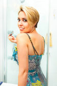 Lachende vrouw in badkamer toepassing lipgloss — Stockfoto