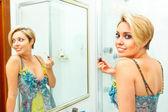 Chica atractiva en baño aplicar lápiz labial — Foto de Stock