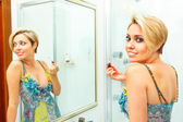 Attractive girl in bathroom applying lipstick — Stock Photo