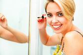 Smiling woman in bathroom applying mascara — 图库照片