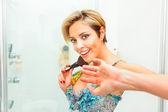 Embarrassed pretty woman in bathroom using fluffy brush — Stock Photo