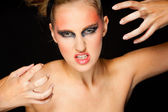 Mysterious woman with extravagant makeup and scaring expression — Stock Photo