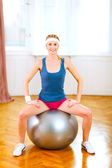 Ince kız fitness topu üzerinde oturan spor giyim — Stok fotoğraf