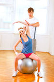Smiling girl making exercises on fitness ball assisted by her pe — Stock Photo