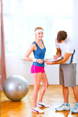Personal trainer measuring belly of girl in sportswear — Stock Photo