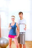 Healthy couple in sportswear showing clipboard with measuring ta — Stock Photo
