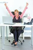 兴奋的商务女人坐在办公室桌前和喜乐她的成功 — 图库照片