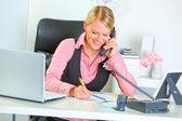 улыбается женщина бизнес говоря телефон и записи в блокнот — Стоковое фото