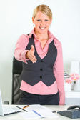 Smiling business woman standing near office desk and stretches out hand for — Stock Photo