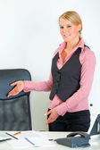 Smiling business woman standing near office desk and inviting to sit on cha — Stock Photo