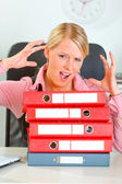 Stressed modern female manager with pile of folders at office de — Stock Photo