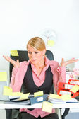 Shocked by set of tasks business woman sitting at workplace covered with st — Stock Photo