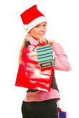 Smiling female business clerk in Santa Hat with shopping bags — Stock Photo