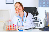 Female medical doctor sitting in cabinet and dreaming — Stock Photo
