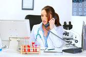Kobieta lekarz danej rozmowy na telefon i patrząc w monitorze — Zdjęcie stockowe