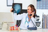 Smiling female medical doctor speaking phone and holding patient — Stock Photo