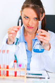 Interested woman researcher working with test tubes in laboratory — Stock Photo