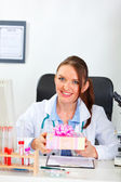 Smiling female medical doctor sitting in office and holding present — Stock Photo
