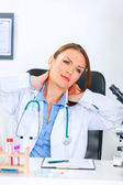 Tired doctor woman sitting at office table and massaging her neck — Stok fotoğraf