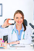 Smiling doctor woman sitting at office table and holding blank business car — Stock Photo