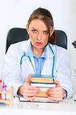 Šokovaný lékař žena sedí u stolu v kanceláři s hromadou knih — Stock fotografie