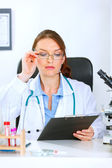 Doctor woman sitting at office table and looking in clipboard — Stock Photo