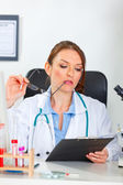 Thoughtful female medical doctor looking in clipboard at cabinet — Stock Photo
