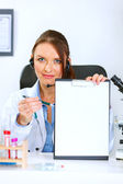 Doctor woman sitting at office table showing blank clipboard and — Stock Photo